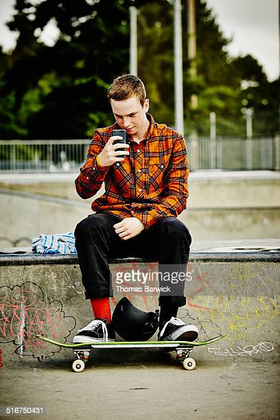 Skateboarder taking a picture with a smartphone