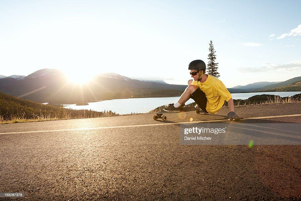 Skateboarder taking turn at sunset.