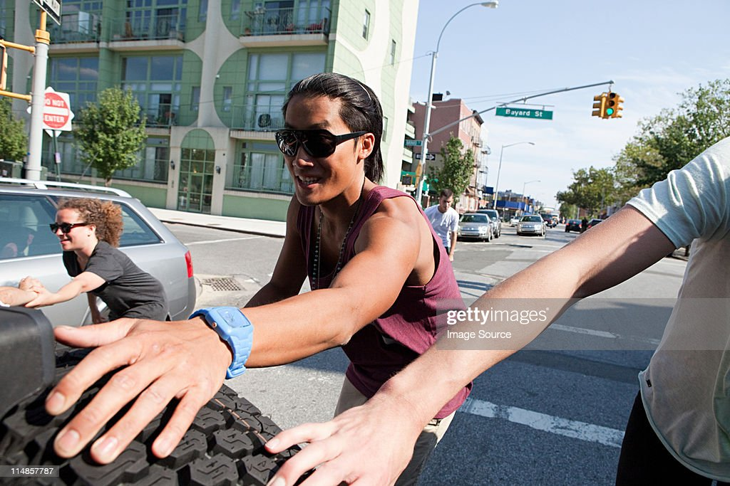 Skateboarders holding on to tyre on back of car : Stock Photo