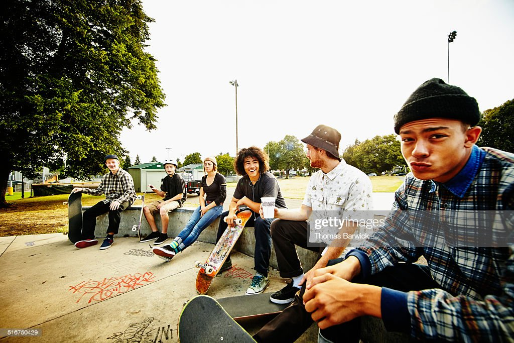 Skateboarders relaxing on edge of skate park