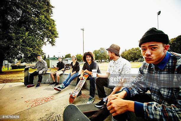 Skateboarders relaxing on edge of skate park