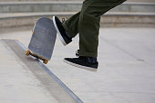 A male falling after doing a rail grind at Venice Skate Park in Venice Beach California