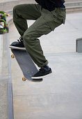 A male jumping up to do a rail grind at Venice Skate Park in Venice Beach California