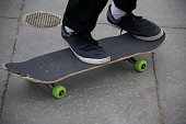 Male riding a skateboard with green wheels at Vencie Skate Park in Venice Beach