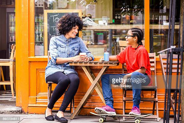 Skateboarding boy and mother sitting at sidewalk cafe