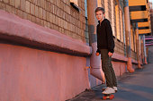 Skateboarding teenager is riding right on sunset city street