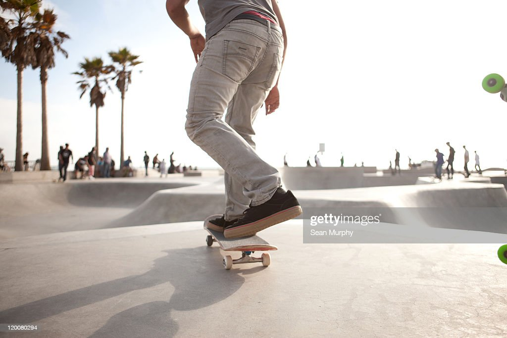 Skater about to skate down a ramp at a skatepark