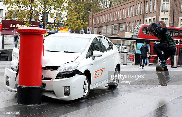 A skater boarder passes a car 'crashed' into a post box outside King's Cross Station in London United Kingdom on November 15 ahead of the launch of...