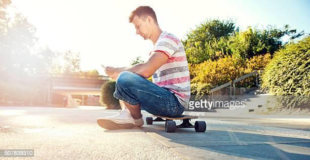 スケート選手を使用している少年携帯電話の ストリート