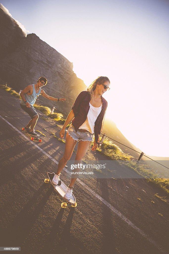 Skater couple longboards road