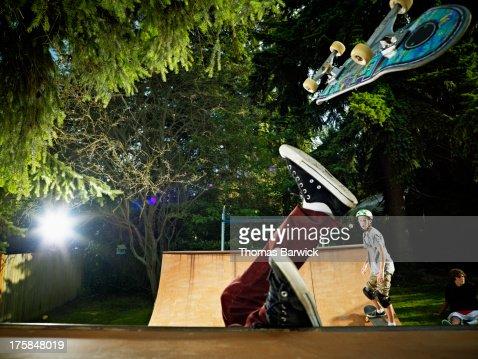 Skater falling off skateboard on backyard halfpipe