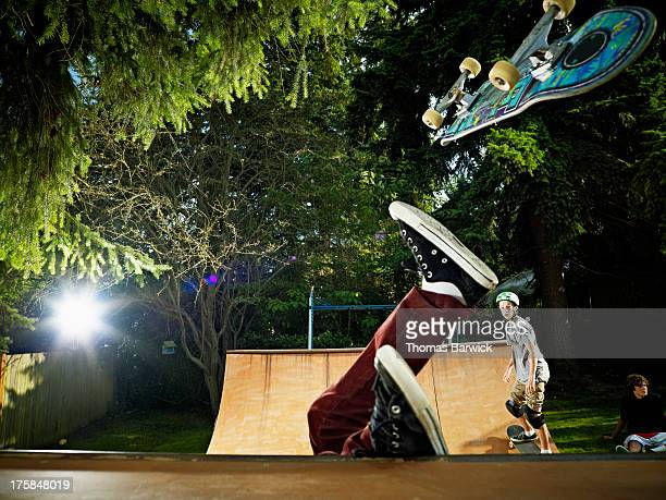 Skater falling off skateboard on backyard halfpipe