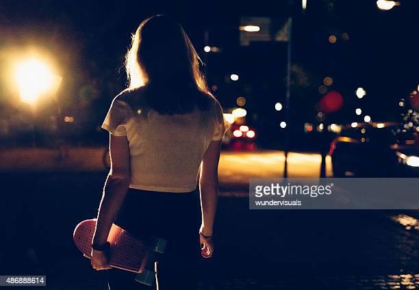 Pattinaggio di Ragazza che cammina da sola con il suo skateboard a notte