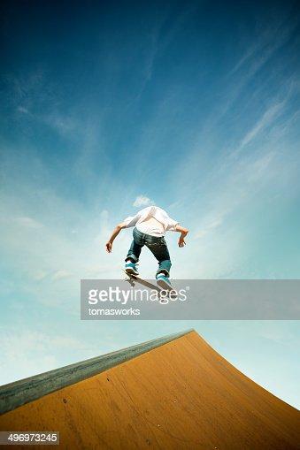skater in jump over skating poligon ramp