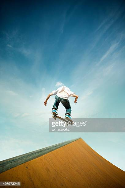 skater in jump over skating poligon ramp