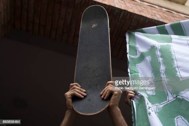 A skater lifts a skateboard during a vigil in tribute to Ignacio Echavarria a victim of the London terror attack outside of Las Rozas City Council on...