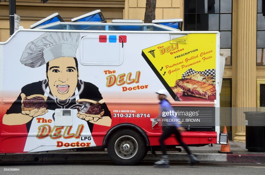 A skater moves past a parked food truck in Hollywood, California on May 25, 2016. A recent Los Angeles Times analysis of data from the LA County of Public Health found that in the past two years some 27 percent of food trucks operating in southern California were unable to obtain an 'A' rating, amid concerns of sanitary conditions in the confined space. / AFP / FREDERIC