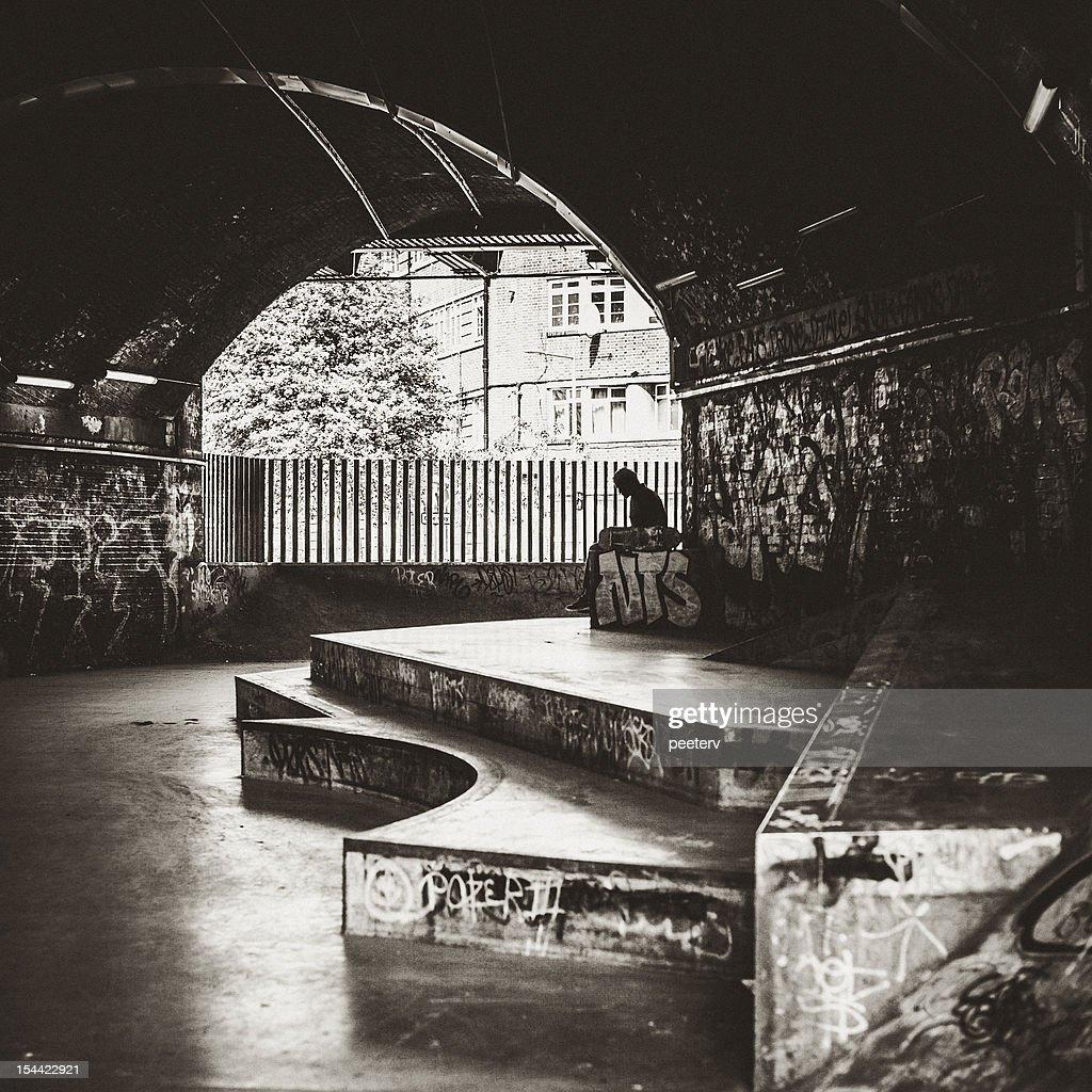 Skater sitting alone at skatepark. : Stock Photo