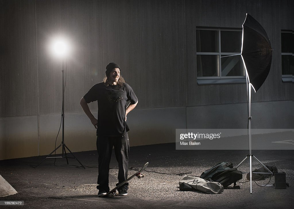 Skater standing under photo lights