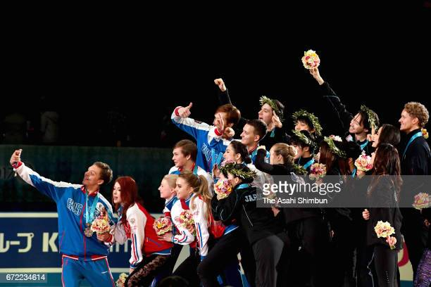 Skaters from Russia Japan and the United States pose for selfie photographs after the medal ceremony during day three of the ISU World Team Trophy at...