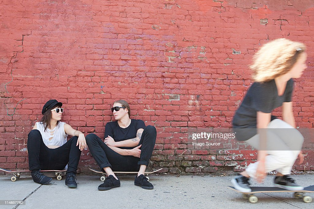 Skaters sitting on boards as other skater goes past : Stock Photo