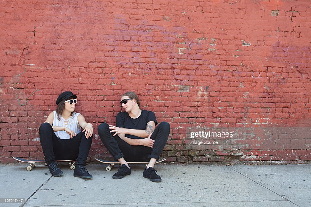 Skaters sitting on boards by wall : Stock Photo