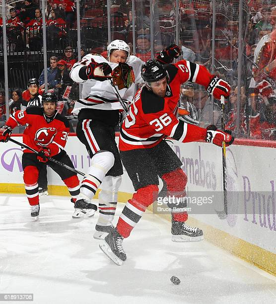 Skating in his first NHL game Nick Lappin of the New Jersey Devils hits Brian Campbell of the Chicago Blackhawks during the second period at the...