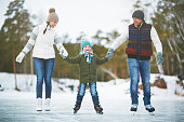 Cute boy and his parents skating together on the rink