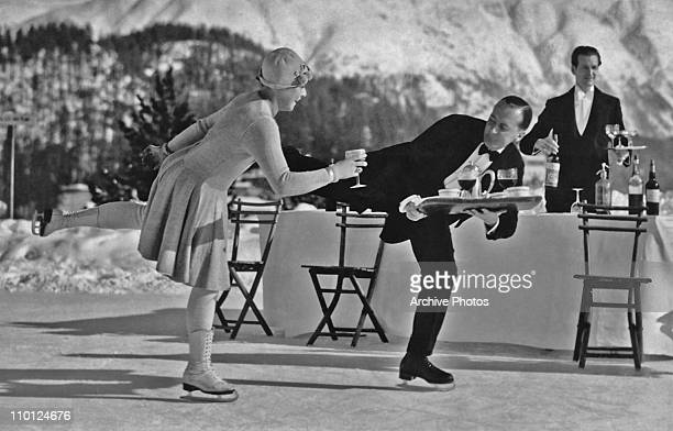 Skating waiters serve drinks to guests on the ice rink at the Grand Hotel in St Moritz Switzerland circa 1925