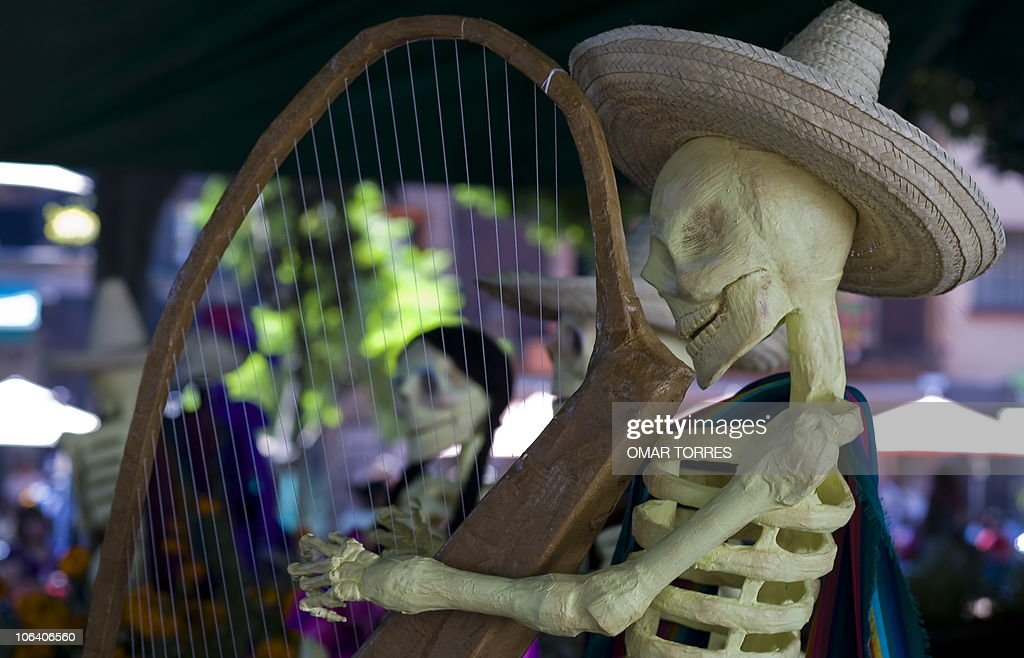 A skeleton as representation of the dead playing a harp in an Altar of the Dead at one of the parks in Mexico City on October 31, 2010. Mexicans celebrate the Day of the Dead on November 1 and 2 in connection with the Catholic holy days of All Saints' Day and All Souls' Day. AFP PHOTO / OMAR TORRES