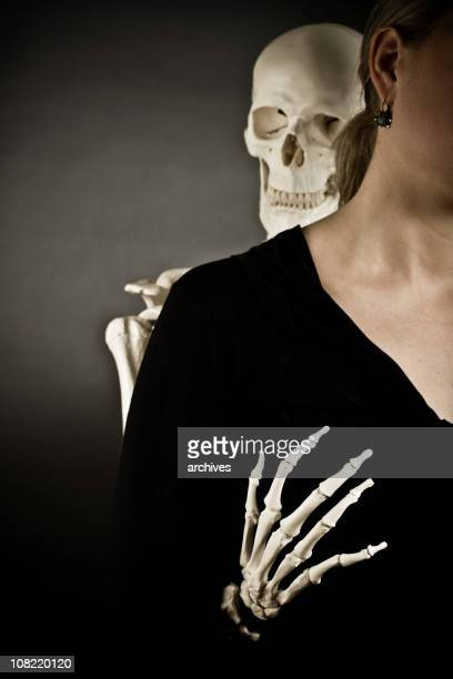 Squelette de femme tenant Suggestively derrière la poitrine.