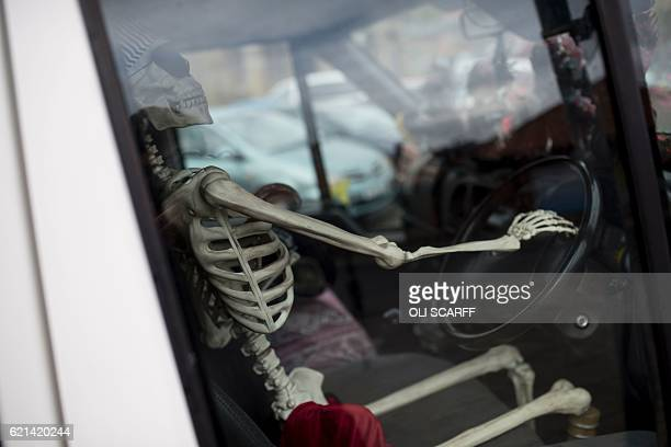 A skeleton is pictured in the driving seat of a parked minibus during the biannual 'Whitby Goth Weekend' festival in Whitby northern England on...