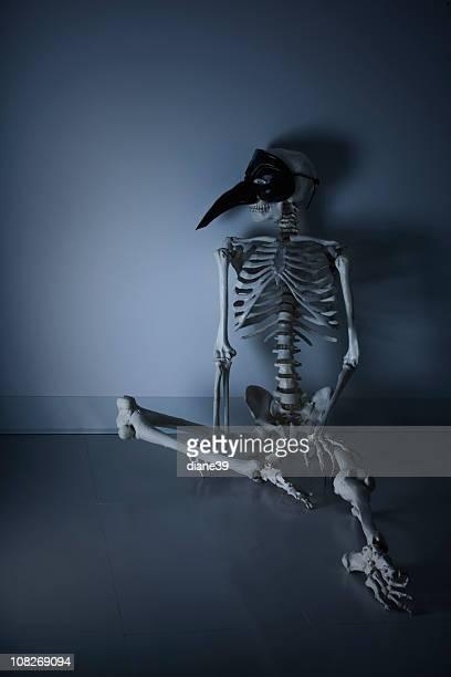 Portant masque et squelette assis contre le mur, discret