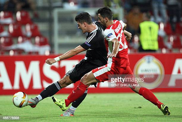 Skenderbeu's Kristi Vangjeli vies with Besiktas' Mario Gomez during the UEFA Europa League Group H football match between KF Skenderbeu and Besiktas...