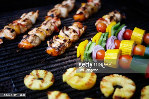 Skewered meats, vegetables and fruits on grill : Stock Photo