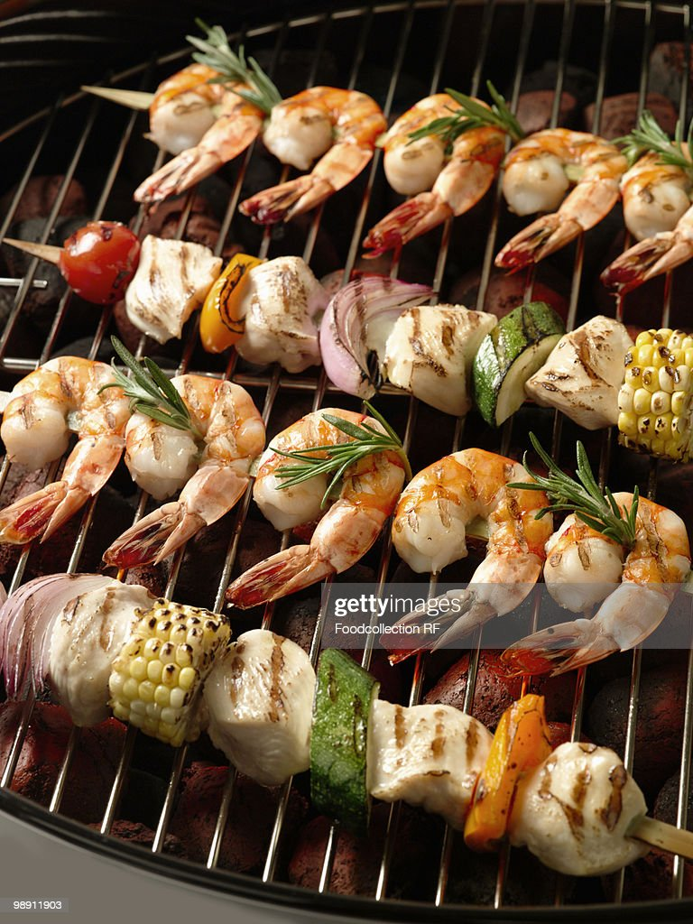 Skewers chicken and prawn kebobs on grill. : Stock Photo