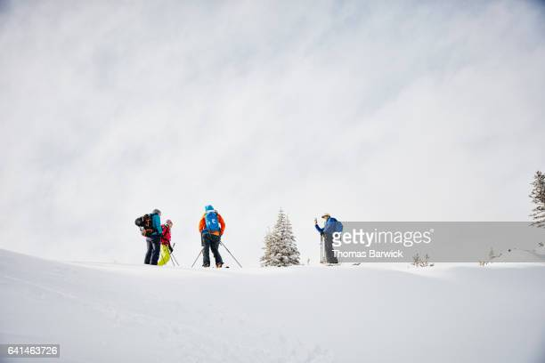 Ski guide taking picture of friends with smartphone while standing on mountain ridgeline
