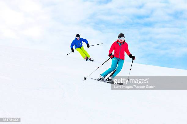 Ski holiday, Two skiers carving donwhill,  Sudelfeld, Bavaria, Germany