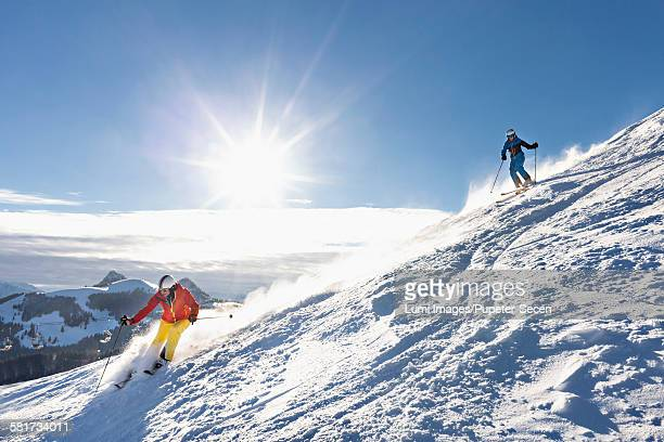 Ski holiday, Two skiers carving downhill, Sudelfeld, Bavaria, Germany