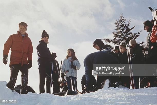 Ski instructor Sigi Engle bends down to fasten the skis of John F Kennedy Jr as his sister Caroline Kennedy mother Jacqueline Kennedy and Senator...