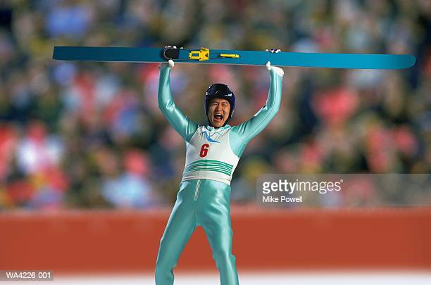 Ski jumper at finish line holding ski in air