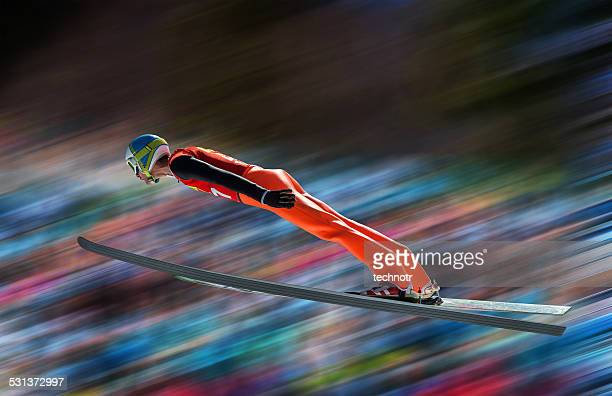 Ski jumper in mid-air against blurred background