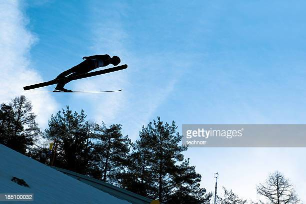 Ski jumper in mid-air against the blue sky