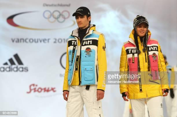 Ski jumper Martin Schmitt walks with Ski alpine athlete Viktoria Rebensburg on the catwalk during the presentation of the German athletes Winter...