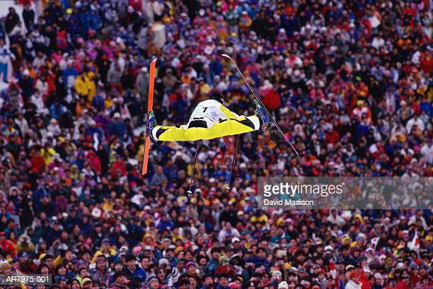 Ski jumper performing freestyle jump, crowd in background