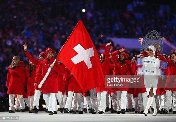 Ski jumper Simon Ammann of the Switzerland Olympic team carries his country's flag during the Opening Ceremony of the Sochi 2014 Winter Olympics at...