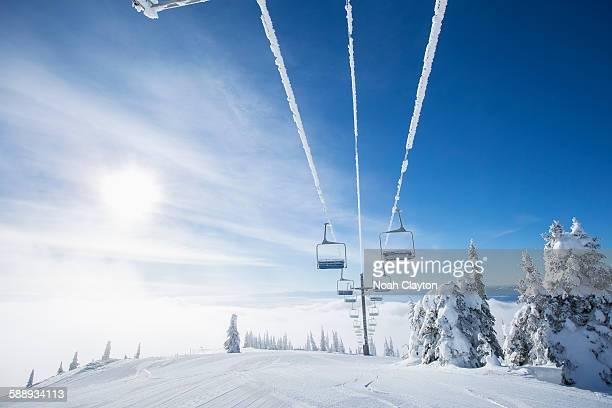 Ski lift at sunlight against blue ski