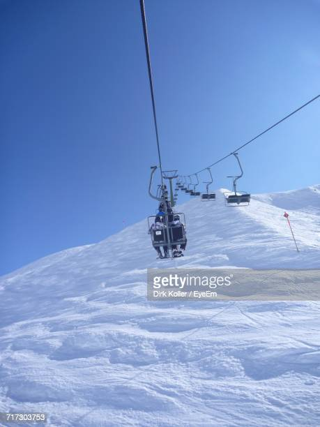 Ski Lift On Snow Covered Mountain Against Clear Sky