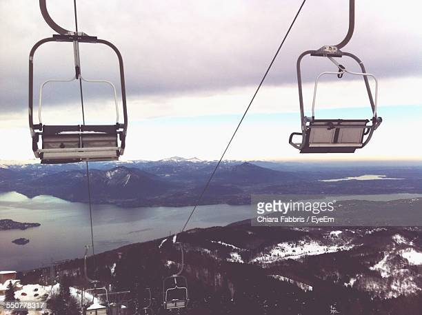 Ski Lift Over Mountains Against Cloudy Sky During Winter