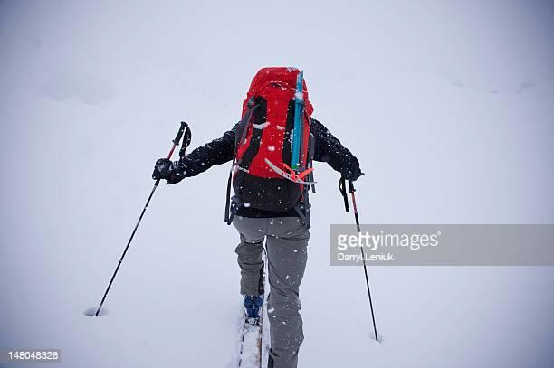 Ski mountaineer climbing a slope through cloud